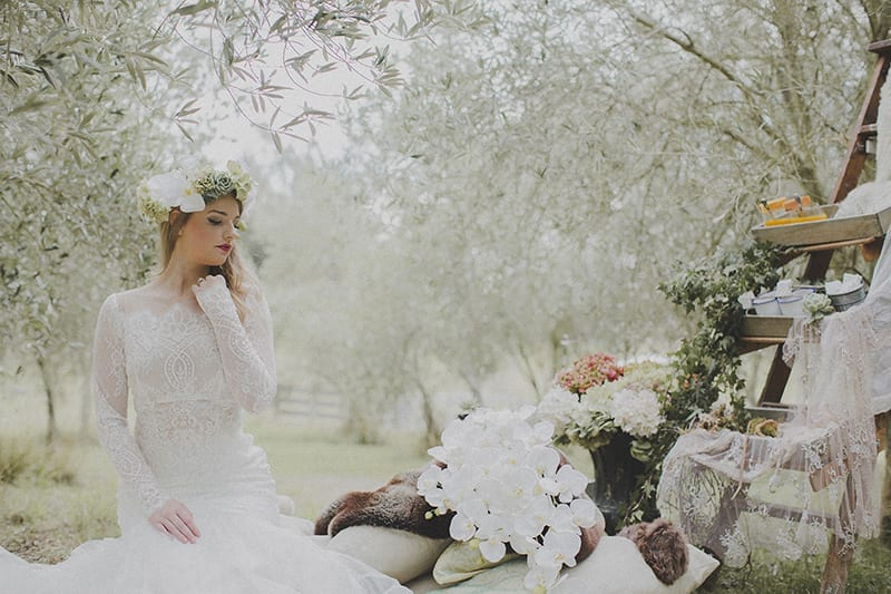 KimChan Events| Bride sitting with cushions and fur  in olive Grove with phalenopsis orchids, ladder decorated with flowers