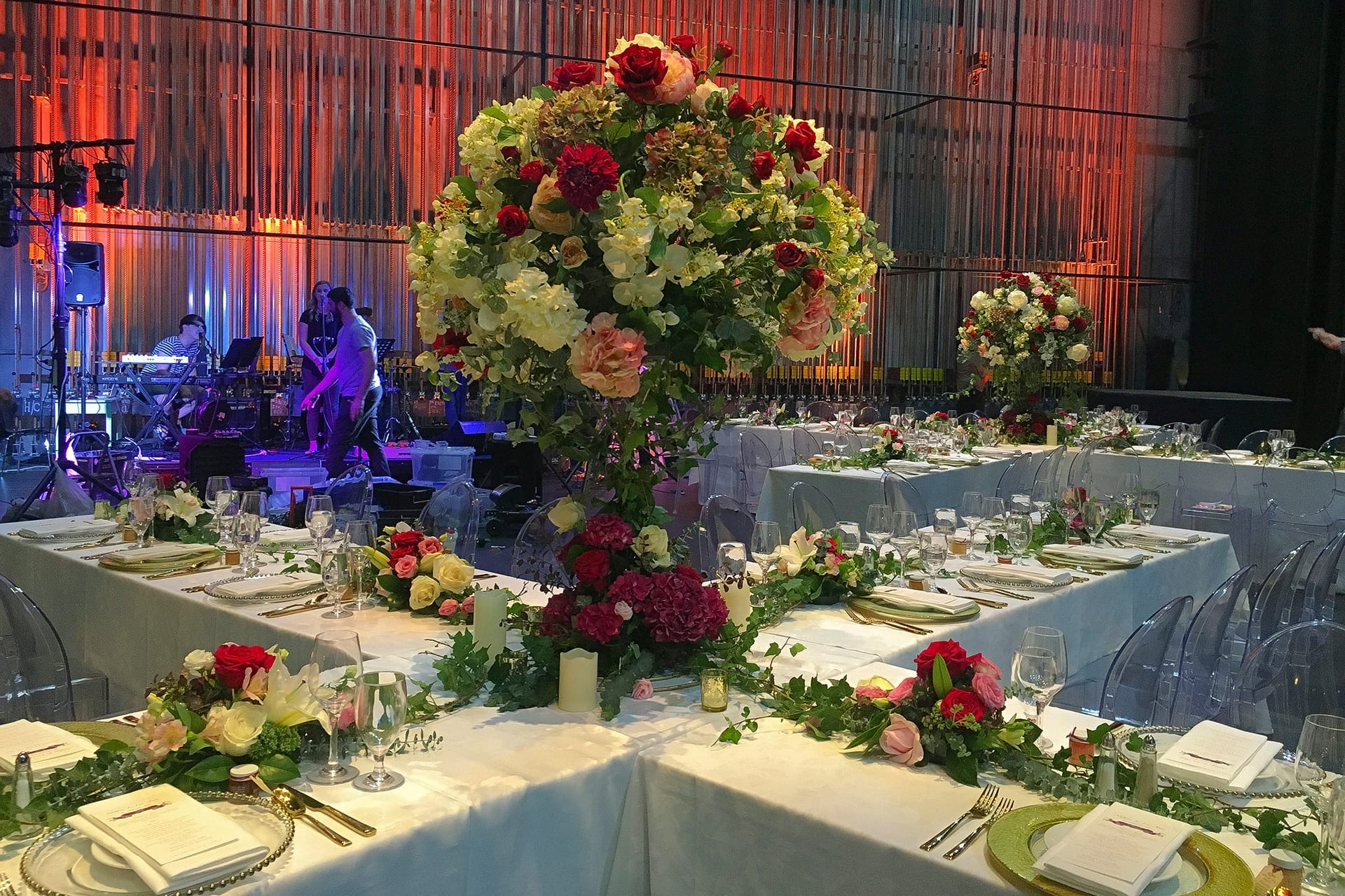 Kim Chan Events| Tall candelabra style arrangements  of orchids roses ad hydrangeas in colours of raspberry  pink and white at centre of x  with long garlands of flowers