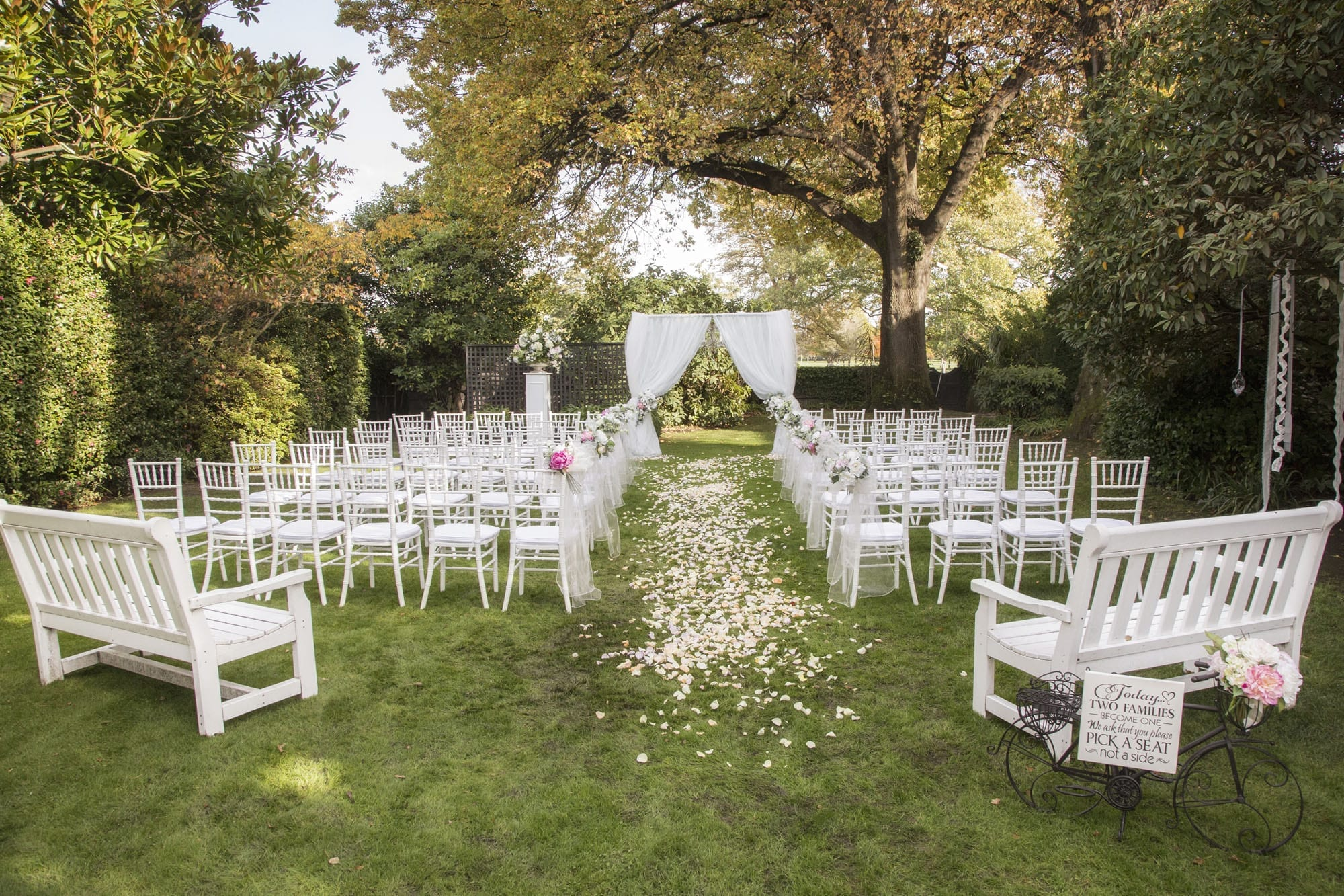 Kim Chan Events | Ceremony area with Archway and drape, flowers on chair ends in garden setting with large trees