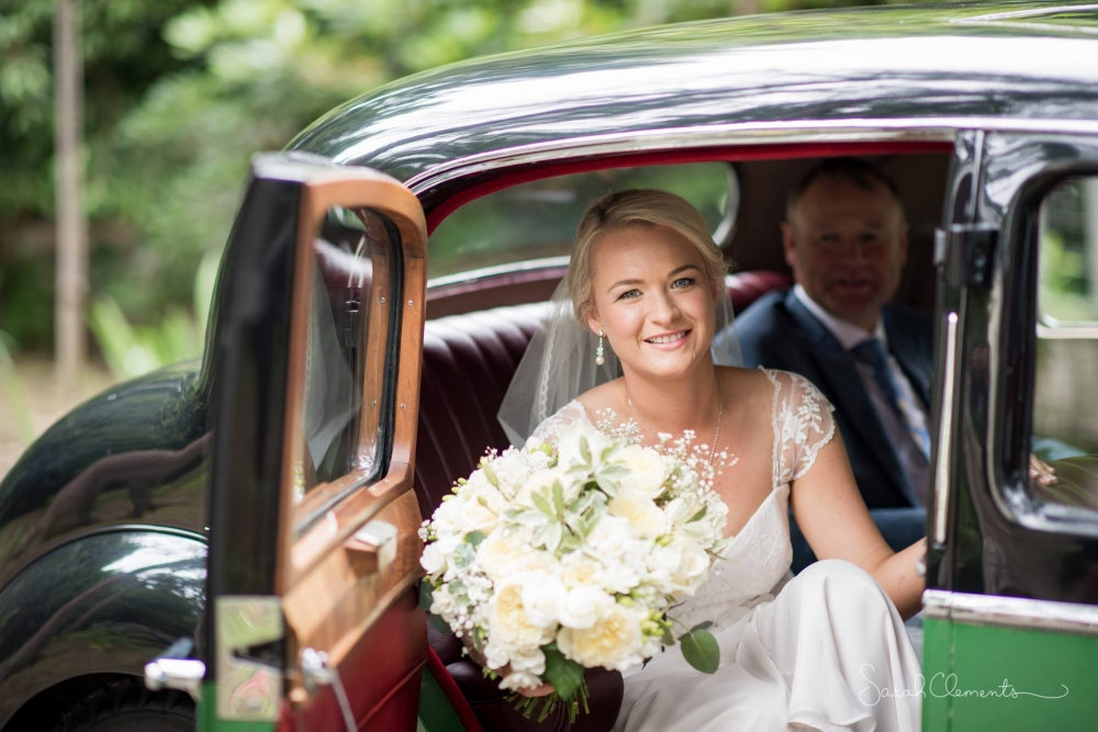 Kim Chan Events|Bride getting out of car carrying Posy bouquet of white roses lizianthus and freesias