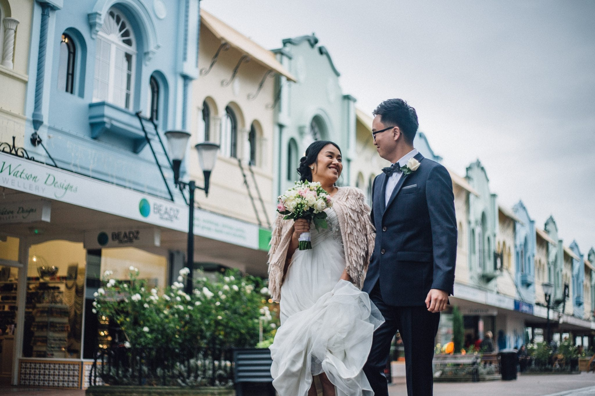 kim chan events | Asian Bride and groom celebrate together after ceremony, carrying bouquet of pink and white blooms, walking down historic New Regent Street,  New Zealand