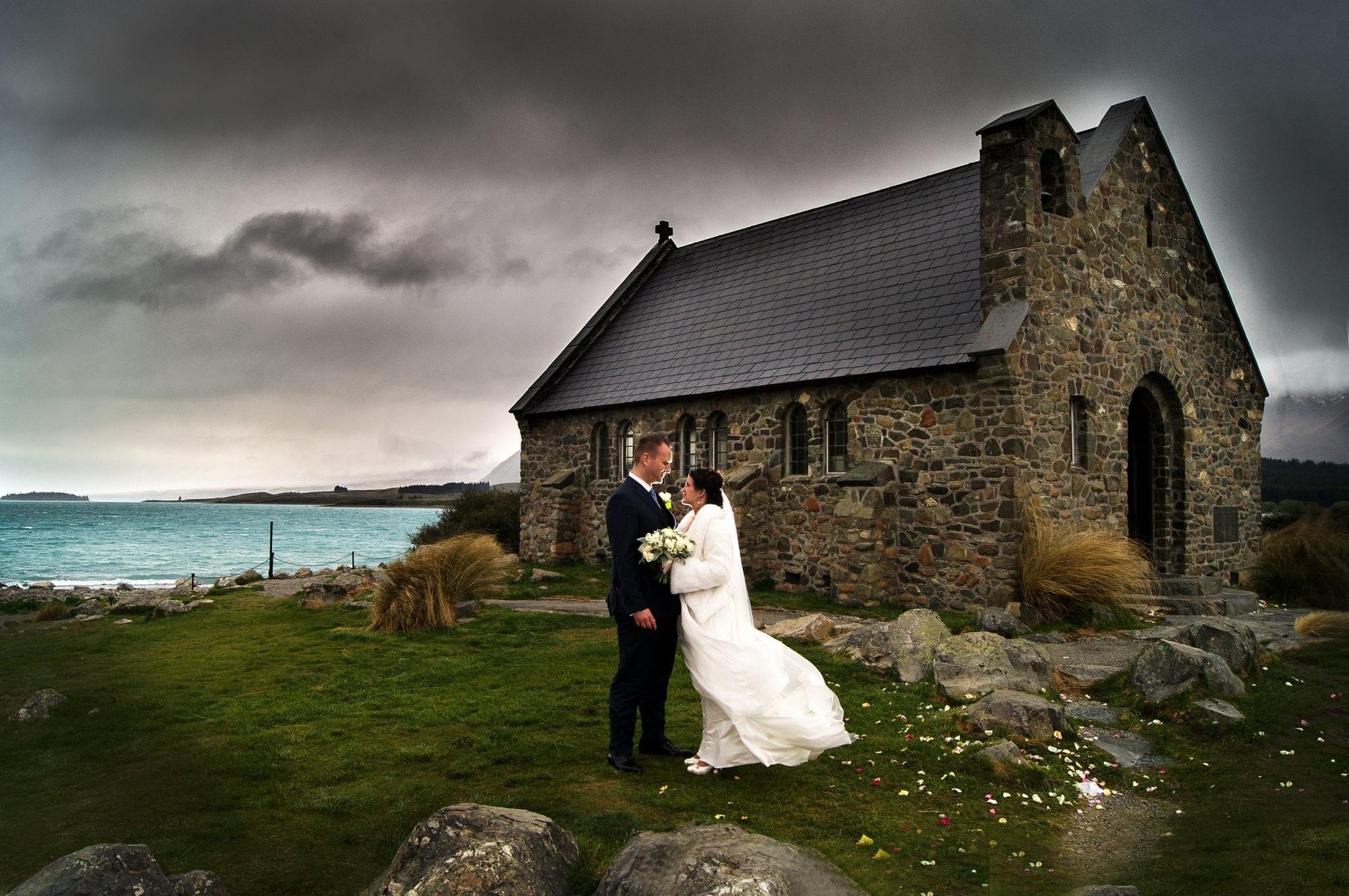 kimchanevents| Amy holding wedding bouquet and Matt at Lake Tekapo Church of the Good Sheppherd