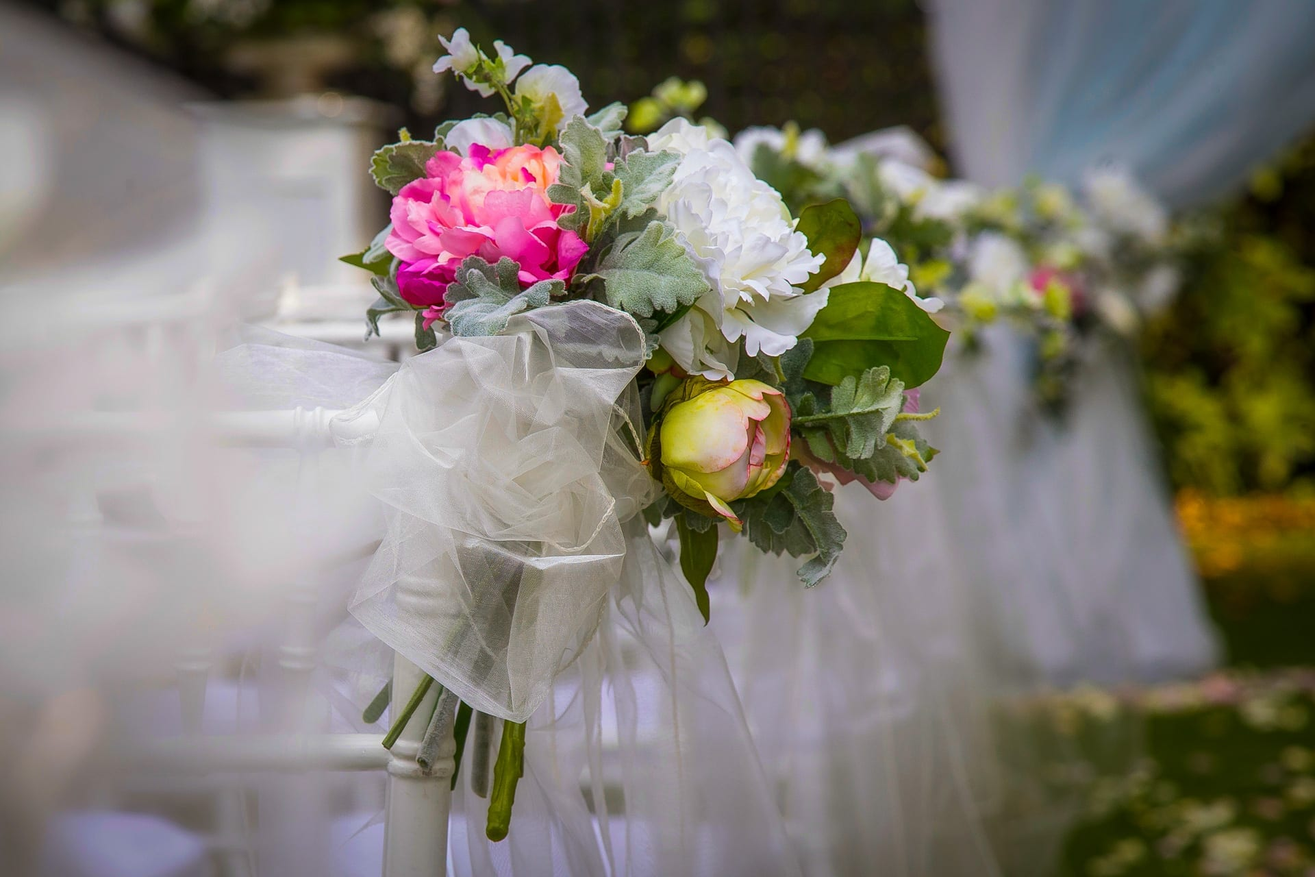 kim Chan Events| asile flowers on chairs with organza bows