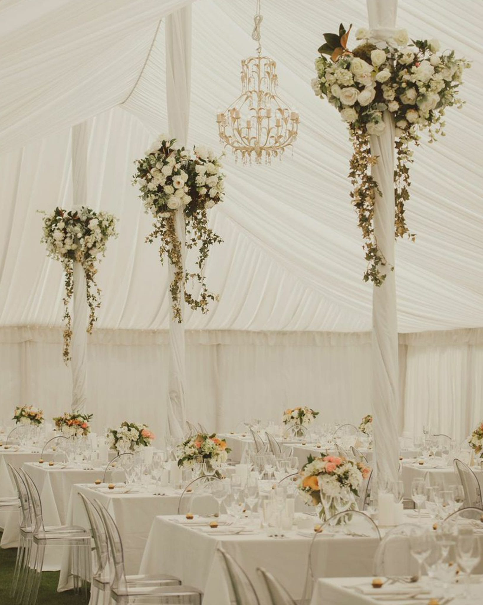 Kim Chan Events| white hanging flowers with gold greenery for poles in Marquee, square tables with bouquets of flowers and clear chairs