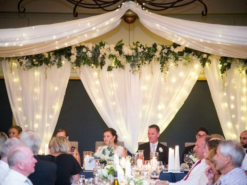 Gorgeous ribbons, fairy lights and flowers above the head table