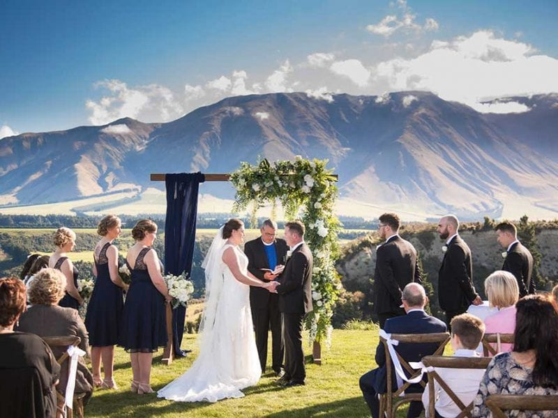 Maddy and Tom are married beneath a gorgeous wedding arch