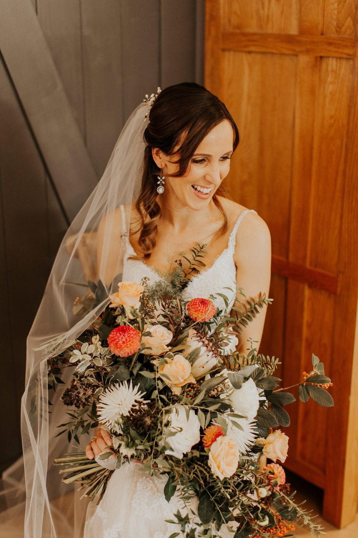 Bride with autumn bouquet of rose hips, proteas dahlias, and foraged greenery by Kim Chan Events