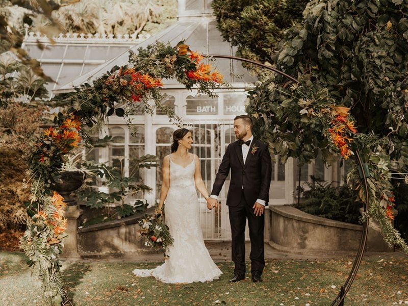 Bride and groom walk beneath stunning wedding arch.
