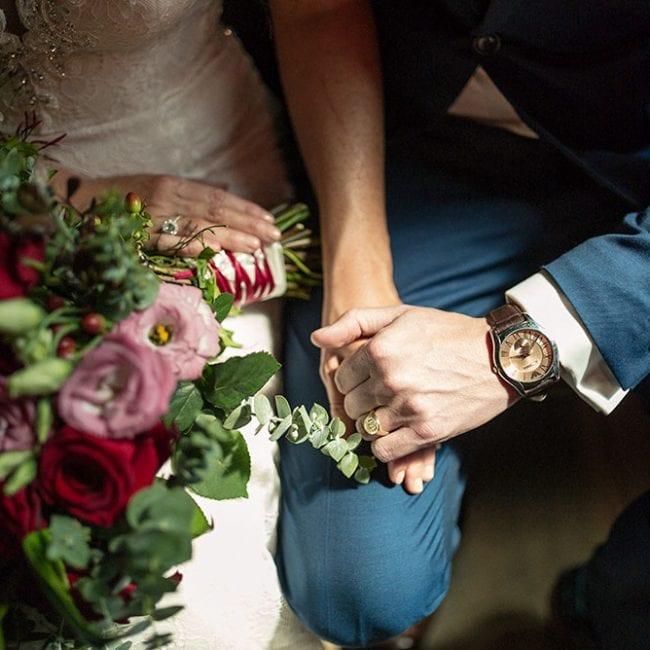 Bride and groom hold hands. Bouquet by Kim Chan Events