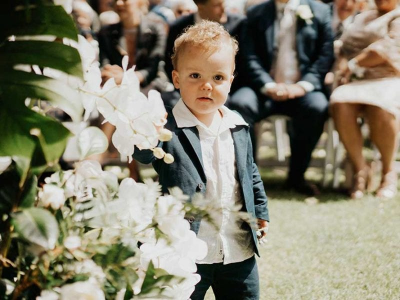 Son at the wedding flower arch