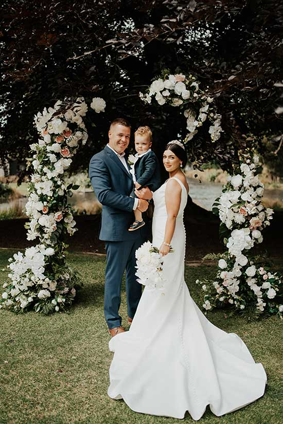 Bride, Groom and their son in front of flower arch