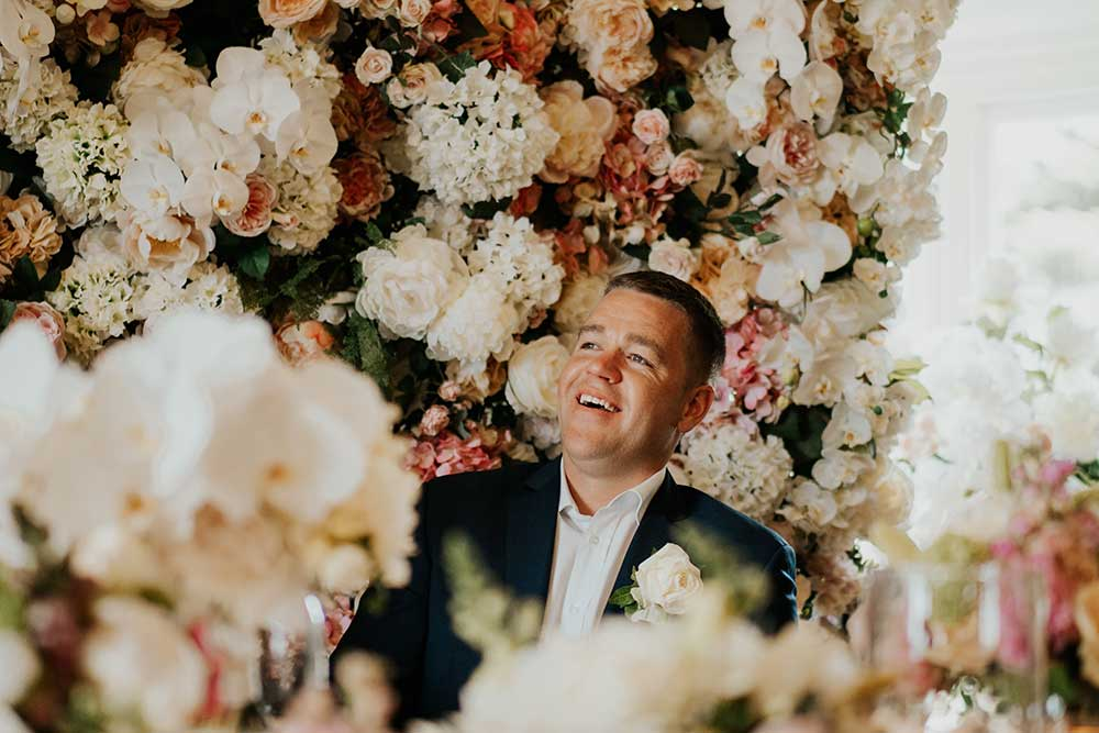 Groom in from of the flower wall
