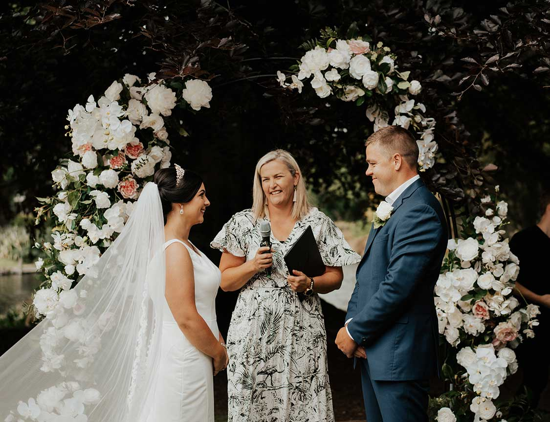 Ashleigh and Reece are married beneath flower arch