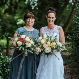 Bride and bridesmaid with their wedding flowers