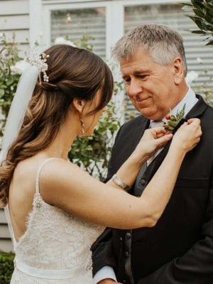 Bride pinning a button hole on her father