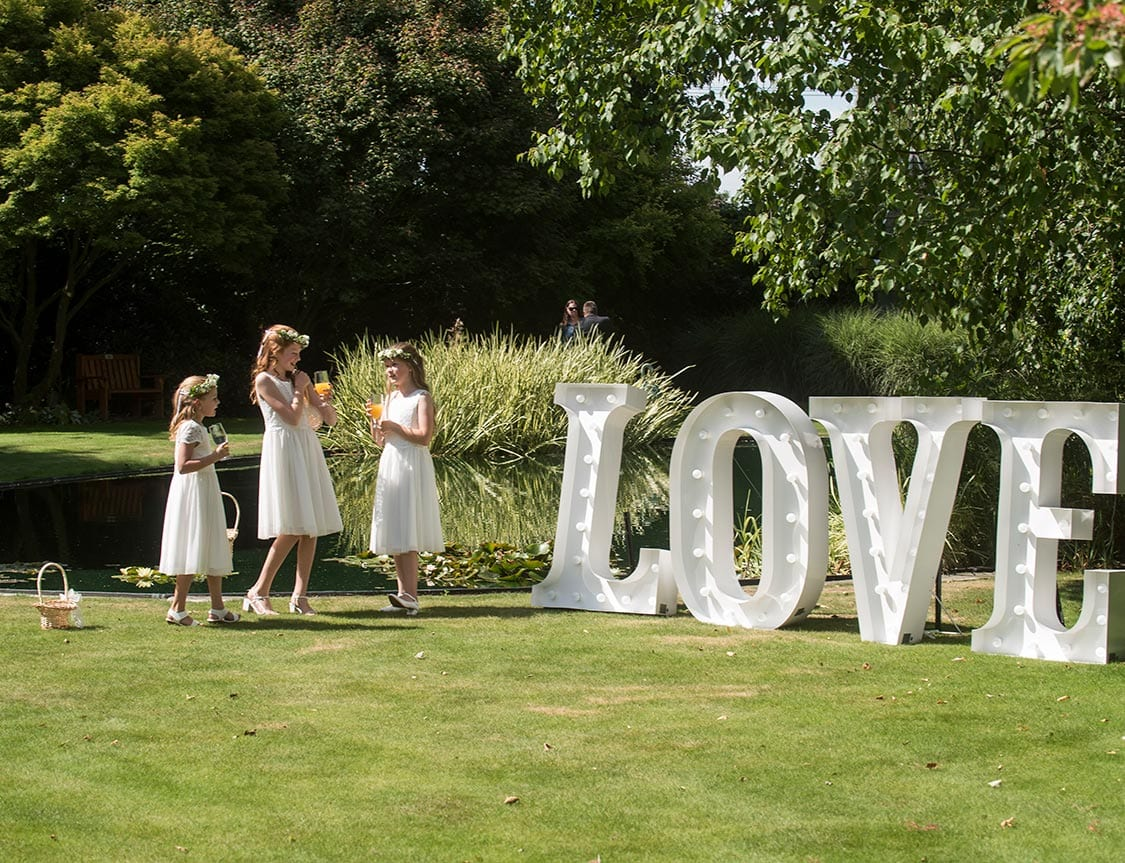 Flower girls play by LOVE sign at wedding