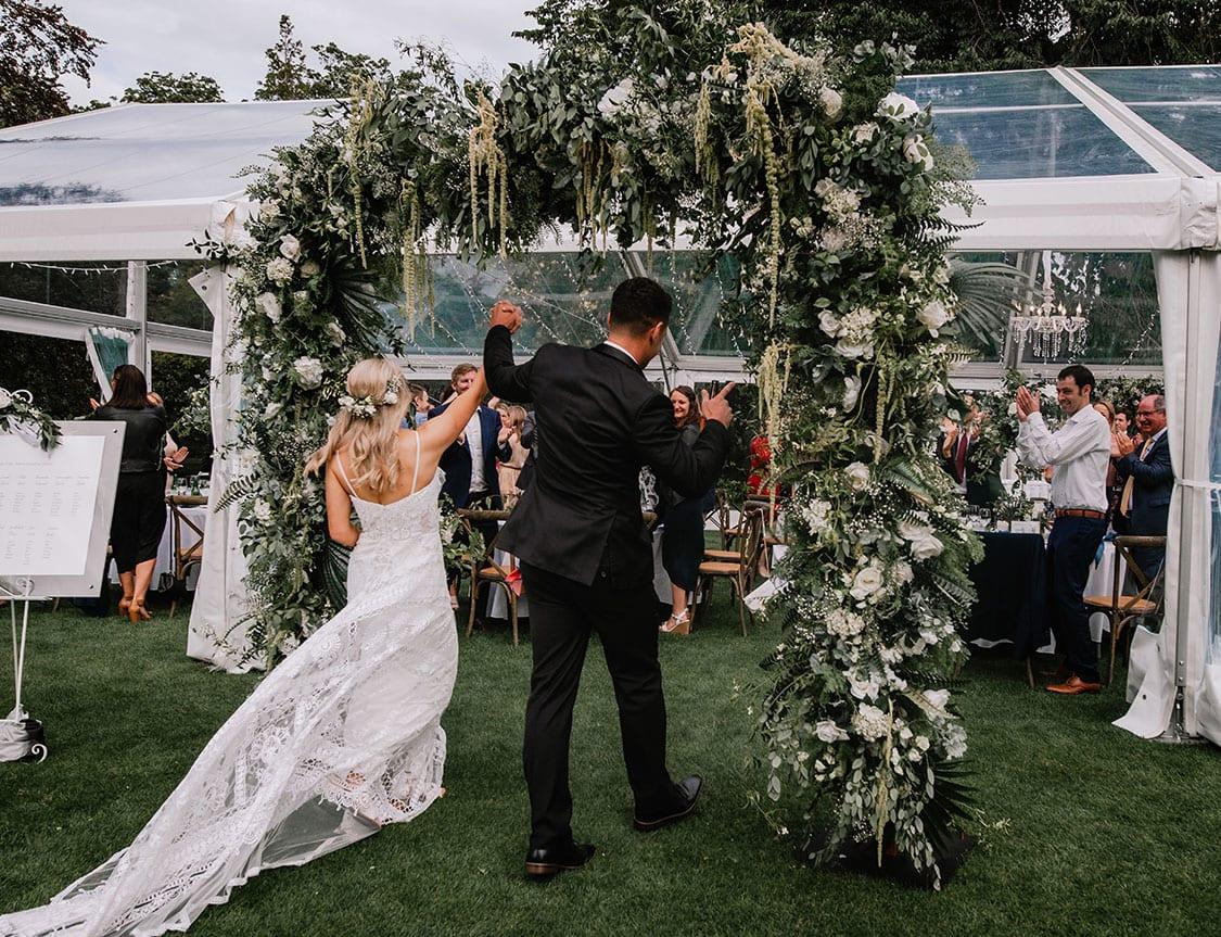 Bride and groom enter through wedding arch