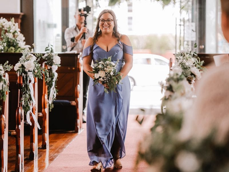 Bridesmaid with bouquet walking down isle of church